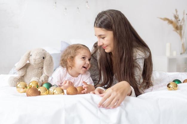 若い母親と一緒に2歳の美しい巻き毛の少女は、花輪と装飾の中でベッドに横になり、笑います