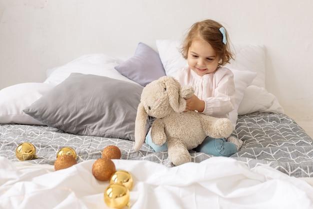 2歳の美しい縮れ毛の女の子がクリスマスライトと装飾と笑いの中でベッドに横たわっています。