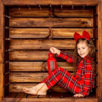 Красивая милая жизнерадостная девушка в красной рождественской пижаме на деревянном фоне держит в руке фонарь