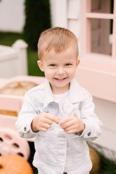白い服を着た美しいかわいい4歳の男の子は、カボチャと白い木造の家の近くで外で遊ぶ