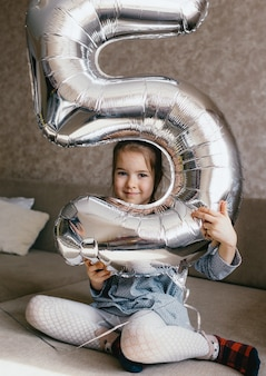 美しいかわいい女の子は、子供の誕生日の5番目の大きな膨脹可能な数を保持しているソファに座っています