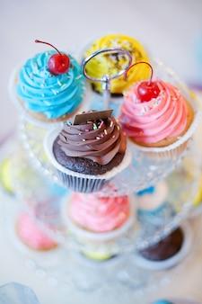 あなたの朝の朝食のための美しいデザート。色とりどりのカップケーキ。
