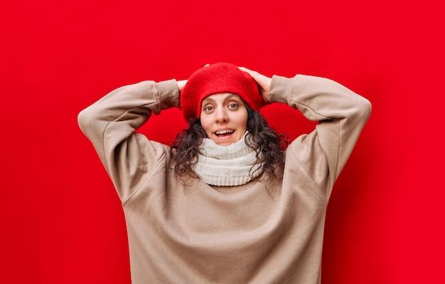 팔을 제기하고 고립 된 붉은 벽으로 머리에 손을 웃는 아름다운 우아한 즐거운 여자