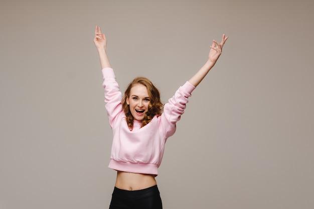 아름다운 감정적 인 소녀가 행복과 회색 배경에서 보는 것에서 손을 들어 올립니다.