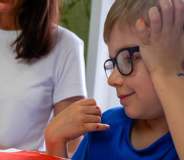 眼鏡をかけた美しいヨーロッパの少年は、母親と一緒に描いた絵をじっくりと見ています。