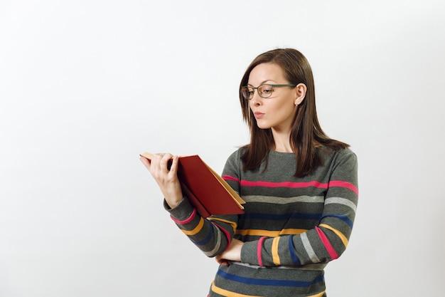 흰색 바탕에 책을 들고 서 있는 화려한 줄무늬가 있는 캐주얼한 짙은 회색 긴팔 옷을 입고 안경을 쓴 아름다운 유럽의 젊은 갈색 머리 여성. 읽기 및 공부 개념