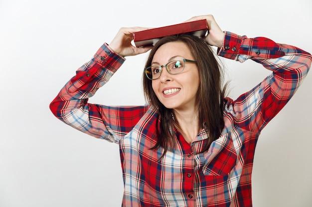 하얀 배경에 책을 들고 서 있는 캐주얼한 빨간색 체크무늬 셔츠를 입은 건강한 깨끗한 피부를 가진 안경을 쓴 아름다운 유럽의 젊은 갈색 머리 여성. 읽기 및 공부 개념