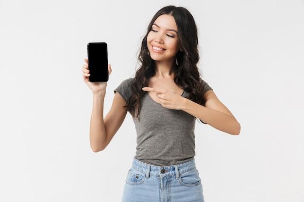 Красивая возбужденная счастливая молодая женщина позирует изолированной над белой стеной, показывающей дисплей мобильного телефона.