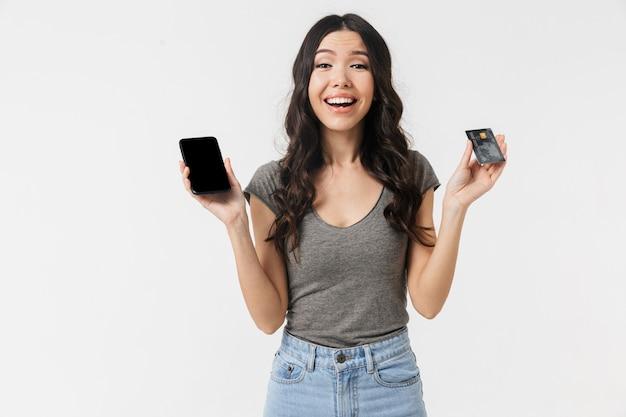 Красивая взволнованная счастливая молодая женщина позирует изолированной над белой стеной с помощью мобильного телефона, держащего кредитную карту.