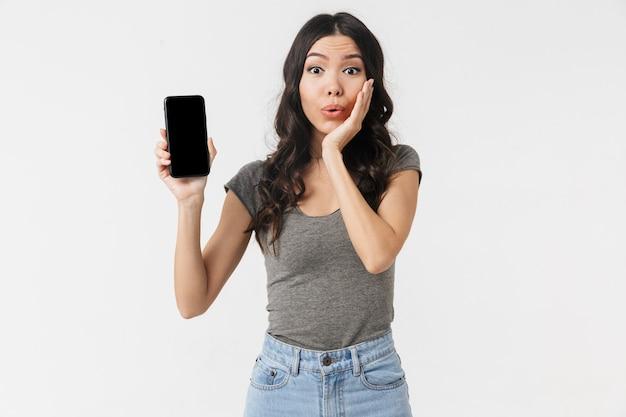 Красивая взволнованная потрясенная молодая женщина позирует изолированной над белой стеной, показывающей дисплей мобильного телефона.