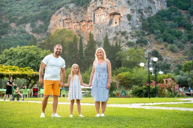 ダルヤン市の山を背景に美しい家族が立っています。トルコのリュキアの墓の近くの人々
