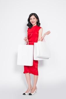 買い物の後、明るいパッケージの横に赤いドレスを着た明るいメイクの美しく、ファッショナブルで豪華な女の子。
