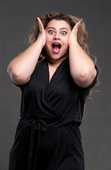 긴 곱슬머리를 한 아름다운 뚱뚱한 여자가 큰 소리로 비명을 질렀다. 분노와 공포의 감정을 가진 통통한 소녀.