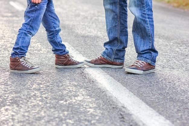 Красивые ноги родителя и ребенка на дороге в парке на природе путешествия