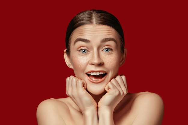 Красивое женское лицо. совершенная и чистая кожа молодой удивленной кавказской женщины на красном фоне студии.