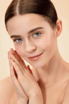 美しい女性の顔。パステルスタジオの背景に若い白人女性の完璧できれいな肌。