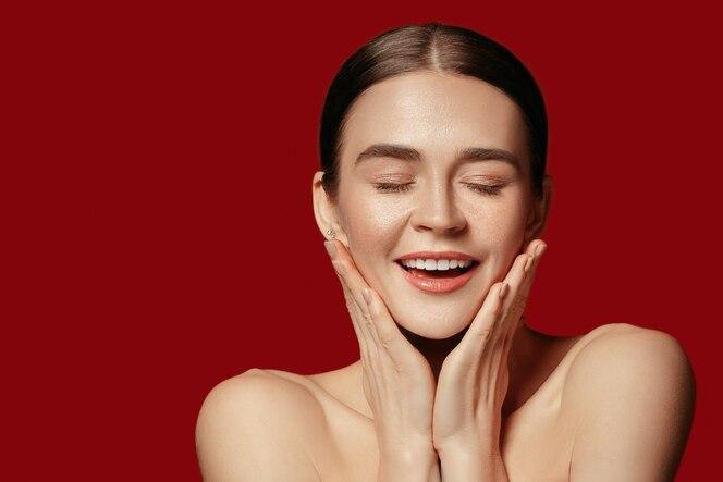 아름다운 여성의 얼굴. 빨간색 스튜디오 배경에 젊은 백인 여자의 완벽하고 깨끗한 피부.