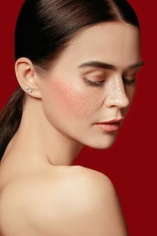 美しい女性の顔。赤いスタジオの背景に若い白人女性の完璧できれいな肌。
