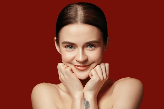 美しい女性の顔。赤いスタジオの若い白人女性の完璧できれいな肌。