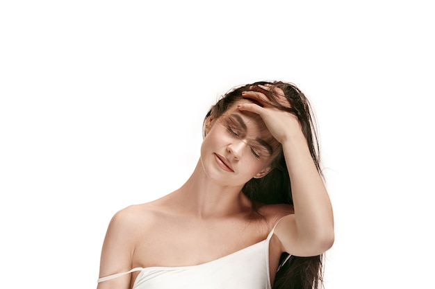 美しい女性の顔。白いスタジオの背景に若い白人女性の完璧できれいな肌。