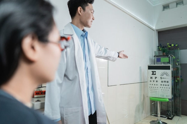 Красивая пациентка делает глазной тест в соответствии с указаниями дежурного врача в палате офтальмологической клиники.