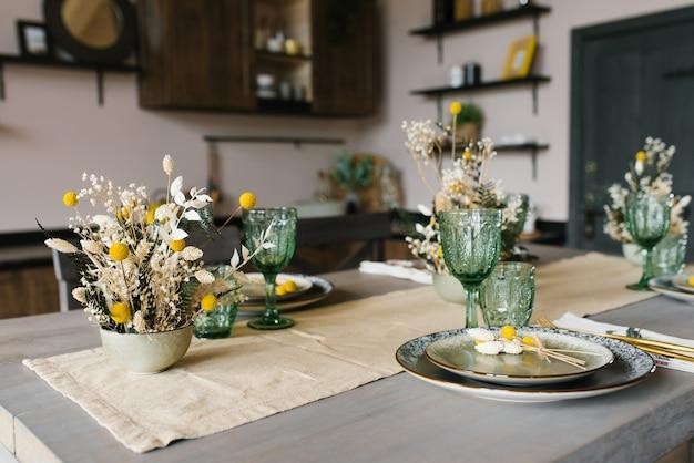 素朴なスタイルの美しいお祭りのダイニングテーブル。テーブルの上の陶製の花瓶のドライフラワー