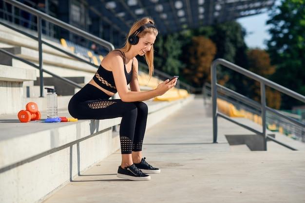 회색 운동복의 아름다운 피트니스 소녀는 스마트 폰을 사용하고 운동 후 경기장에서 음악을 듣습니다. 스포츠와 건강 개념.