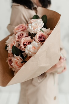 美しい花屋は、ピンクのバラ、灰色の壁の背景に白い花で作られた装飾的な花の美しいカラフルな花束を手に持っています。人工ブーケ。