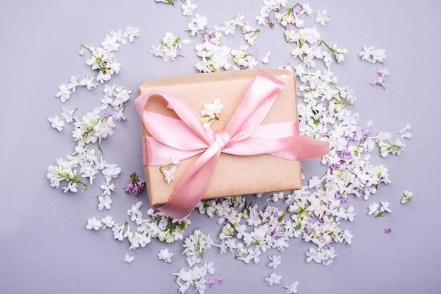 Прекрасный подарок с атласной лентой на фоне сиреневых цветов.
