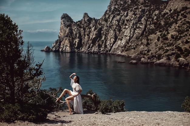 Красивая девушка, невеста, в белом платье сидит на дереве, на скале.
