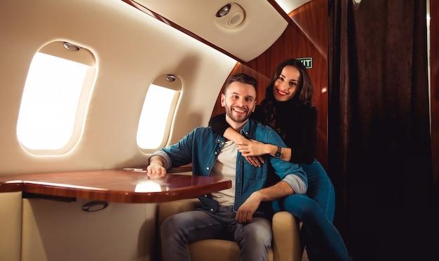 아름다운 소녀와 캐주얼한 복장의 잘 생긴 남자가 개인 제트기를 타고 비행기를 타면서 손을 잡고 웃고 있습니다.