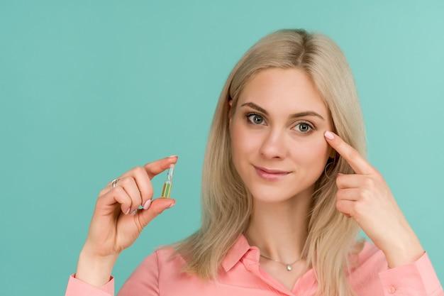 美しい少女ブロガーは彼女の顔に指を示し、アンプルを持っています