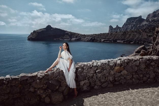 白いドレスを着た美しい少女、花嫁は、崖の上に、石のフェンスに座っています