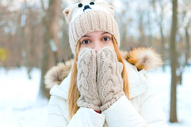 Красивая девушка прикрывает рот руками в перчатках. зимний лес, атмосфера рождества