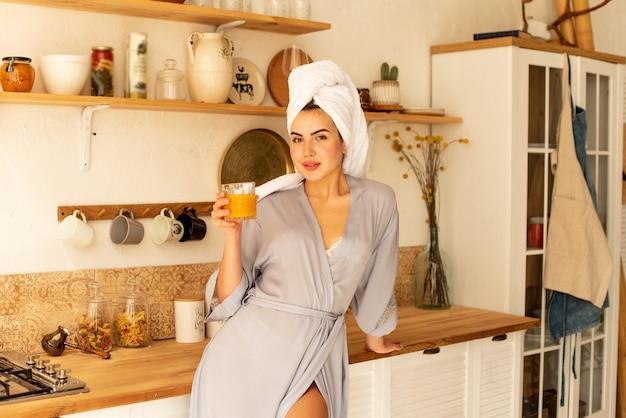 아름다운 소녀가 부엌에서 boho 스타일의 오렌지 주스를 마신다. 그녀는 방금 샤워를 마치고 머리에 수건이 있고 가운을 입고 있습니다.