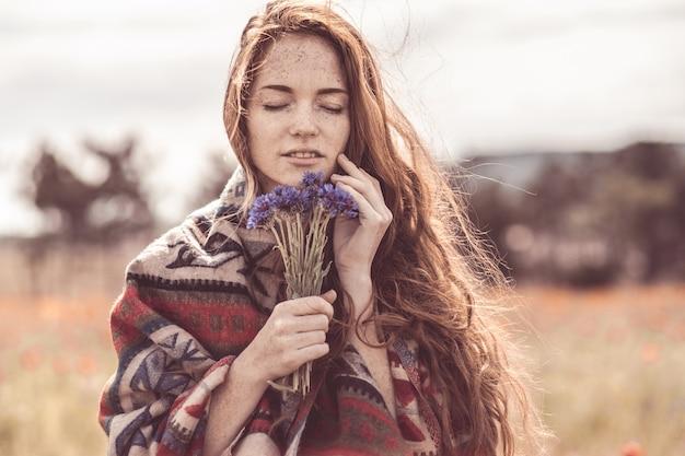 아름다운 소녀가 수레 국화 꽃다발 냄새를 즐깁니다.