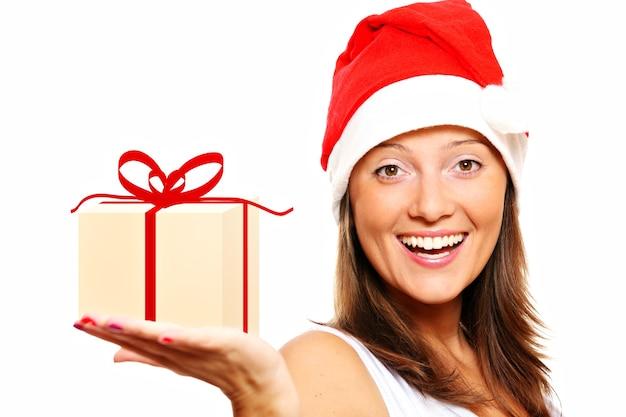 白い背景の上にクリスマスプレゼントを保持している美しい少女