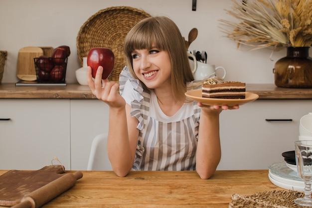 아름다운 소녀는 한 손에는 케이크를, 다른 손에는 사과를 들고 무엇을 먹을지 생각합니다 프리미엄 사진