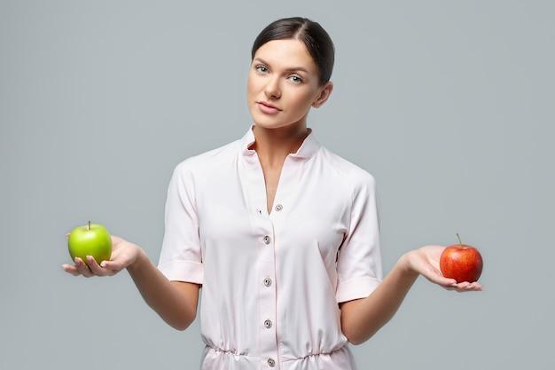 美しい少女は手に緑と赤のリンゴを持っています