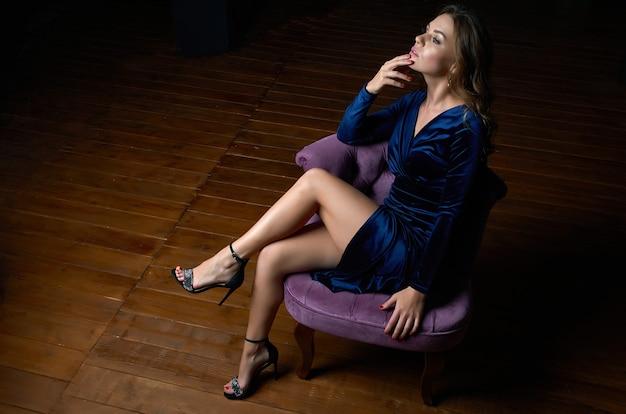 青いドレスを着た美しい少女が暗い部屋の紫色の椅子に座っています。