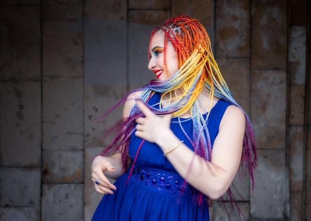 Красивая девушка в ярко-синем платье с радужными африканскими косичками и необычным глиттерным макияжем. кружится и смеется на фоне старого большого здания на теплых улочках весеннего города.