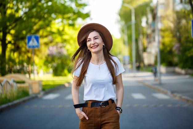暖かい晴れた日に、茶色の帽子と白いtシャツを着た美しい少女が道を歩いています。彼女の顔に笑顔で帽子をかぶった美しい若い女性