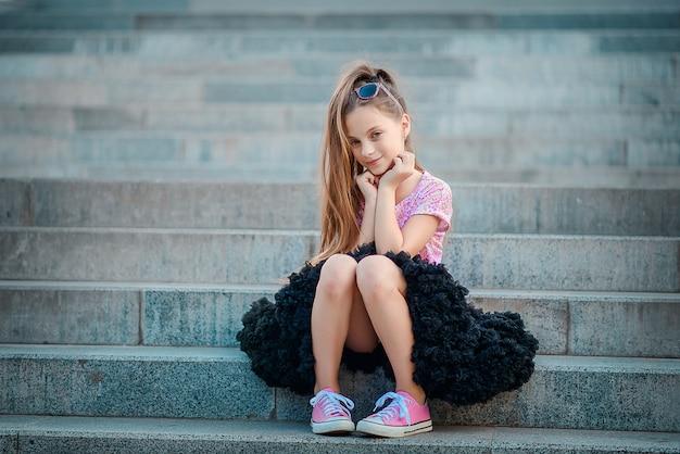 Красивая девушка в пышной черной юбке, пачке и розовых кроссовках сидит на ступеньках.