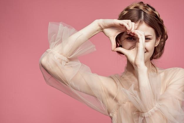 優しいドレスを着た美しい少女は、彼女の手で心と愛と笑顔の兆候を示しています