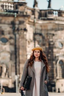 모자를 쓴 아름다운 소녀가 독일 드레스덴의 구시가지에서 타자기와 함께 서 있습니다.