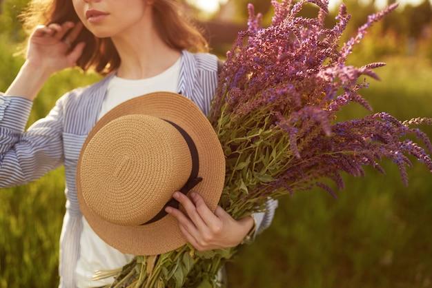 Красивая девушка в шляпе с букетом лаванды. она одета в синюю рубашку, белую футболку и шляпу.