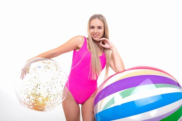 Красивая девушка в розовом купальнике держит два надувных мяча