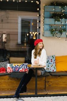 赤いベレー帽の美しい少女は、カフェラテのカップとカフェのテーブルに座って、カップと夢の手を温めます