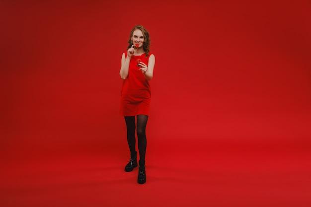 빨간색에 빨간 드레스의 아름다운 소녀는 그녀의 손과 미소에 딸기를 보유하고 있습니다.