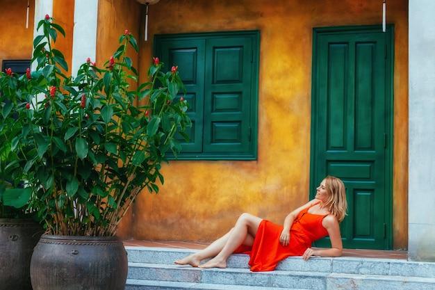 Красивая девушка в красном платье сидит у желтой стены с зеленой дверью и окном с китайскими фонариками. архитектура древнего города хойан. вьетнам.